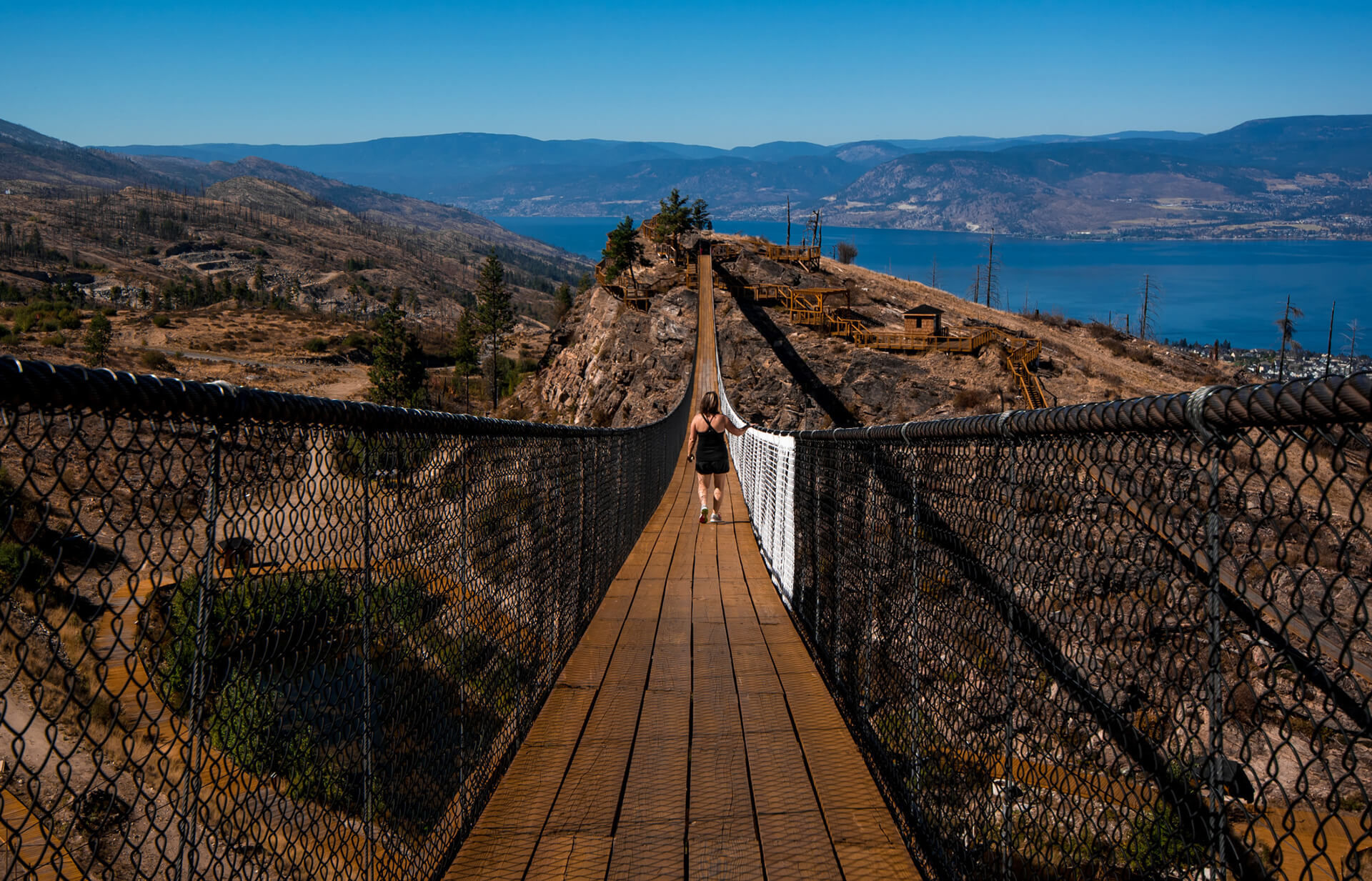 Buying Your First Home In Kelowna - Woman Walking On Hanging Bridge
